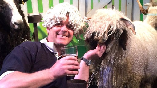 A happy visitor with a beer saying hello to a sheep