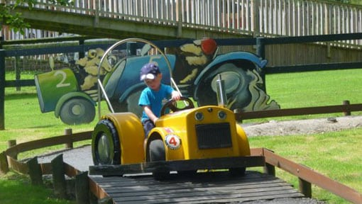 A young boy having fun on a yellow Tractor Ride