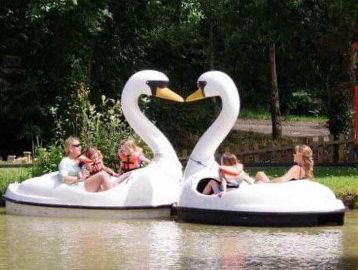 A family enjoying the Swan Lake Pedalos