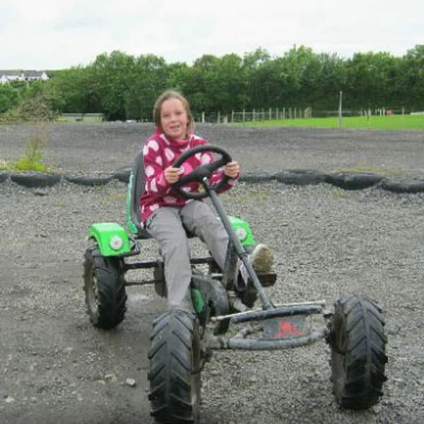 A young girl smiling on a go-kart