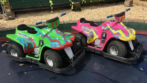 Brightly coloured electric quad bikes on the track
