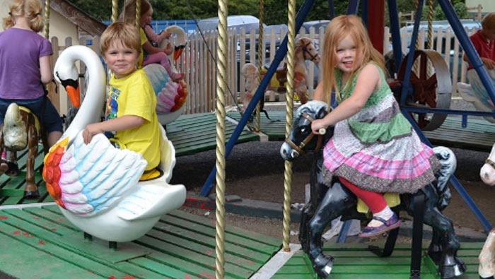 Children having fun on the vintage pony carousel