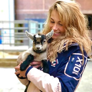 A pretty blond woman smiling and holding a Lamb