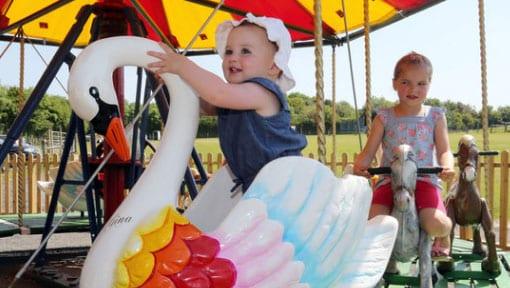 Toddler having fun on the vintage pony carousel