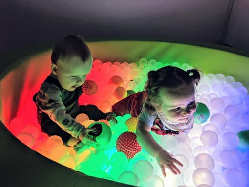 Toddlers having fun in a glowing ball pit at a pre-school class